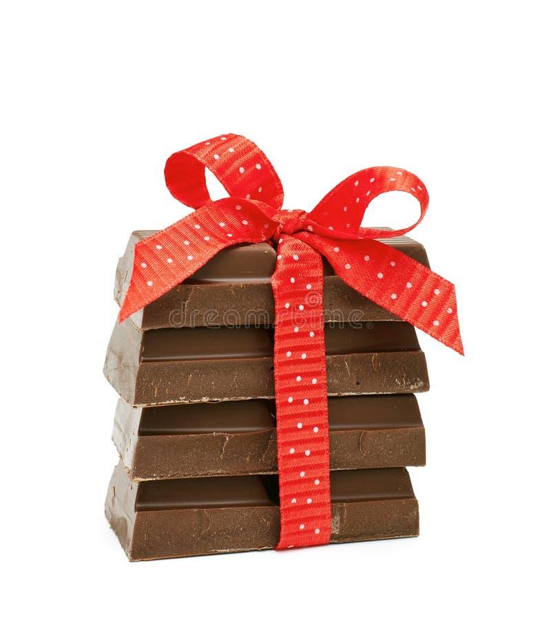 Cioccolato legato con un arco rosso immagine stock