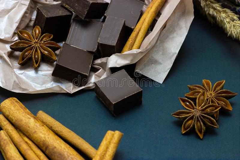 Cioccolato naturale con i fiori cannella e anice stellato della lavanda su un fondo scuro immagini stock libere da diritti