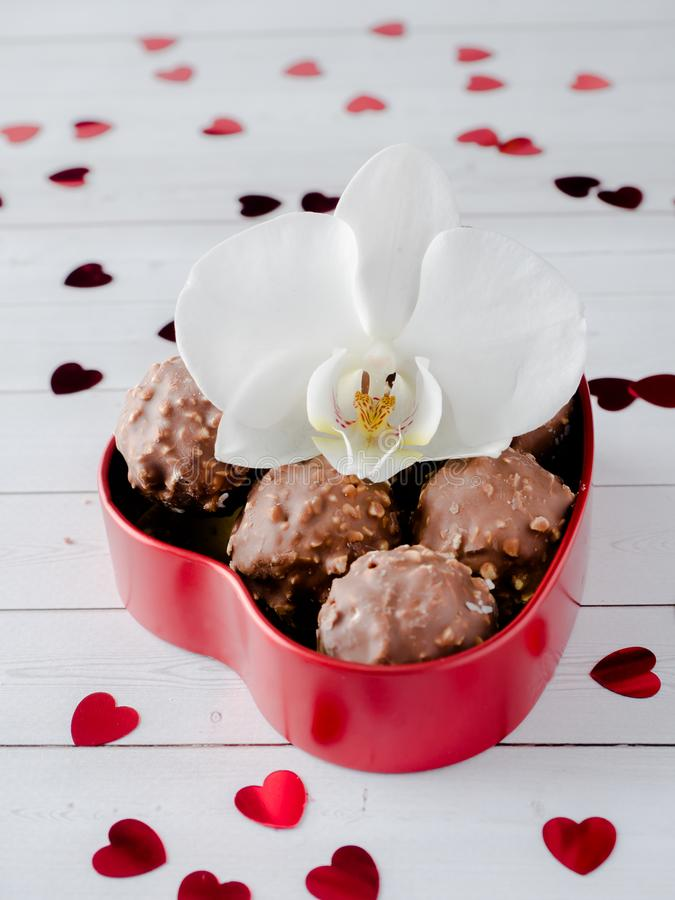 Cioccolato in un fondo di legno bianco del cuore di caffè dell'orchidea rossa della tazza fotografie stock