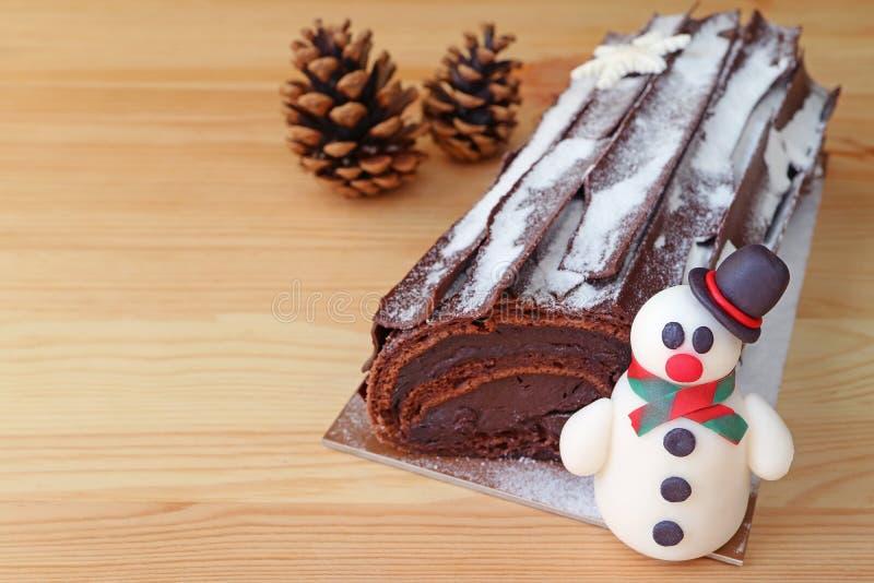 Cioccolato Yule Log Cake per il Natale o Buche de Noel con un marzapane sveglio del pupazzo di neve e due Pin Cones asciutto fotografia stock