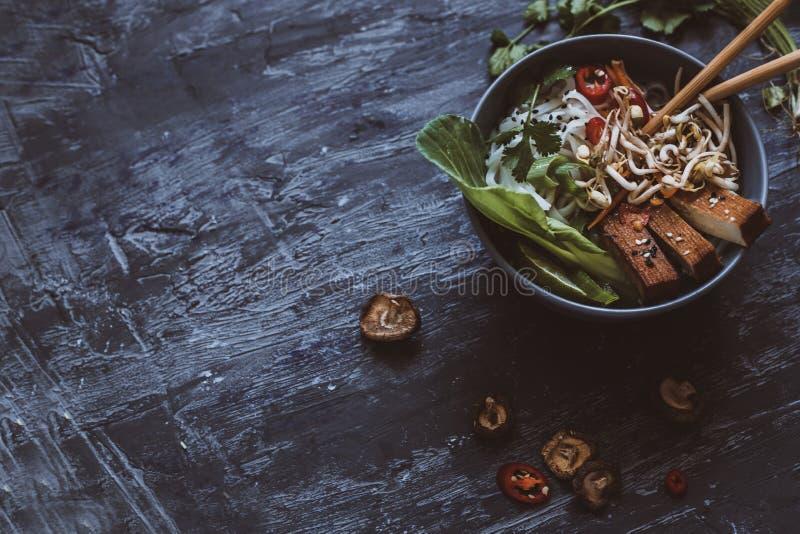 Ciotola asiatica deliziosa con le tagliatelle di riso, le verdure ed il tofu su w immagini stock libere da diritti