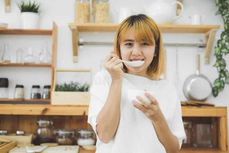 Ciotola asiatica della tenuta della donna di minestra di verdure di riscaldamento della crema della zucca nella sua cucina a casa fotografia stock libera da diritti
