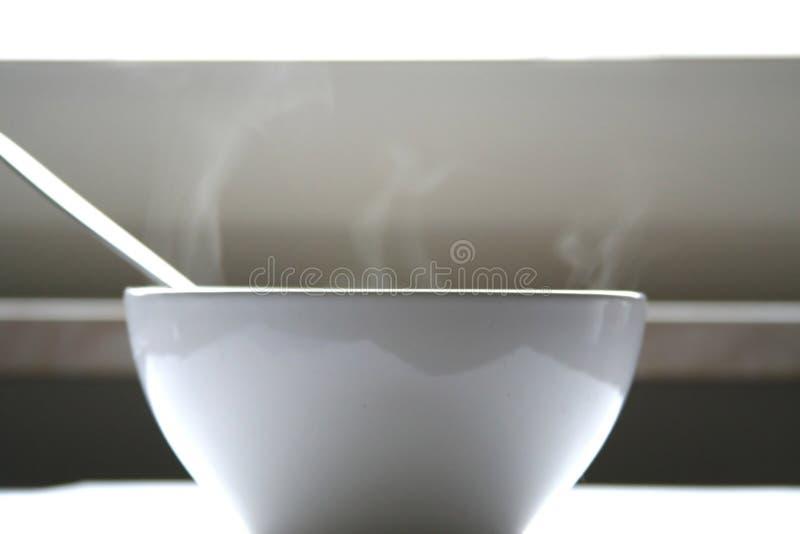 Ciotola bianca con la cottura a vapore minestra e del cucchiaio immagine stock libera da diritti