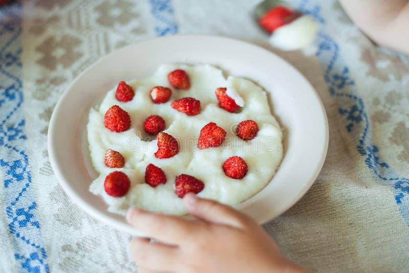 Ciotola bianca di porridge del semolino con le fragole sulla tavola di legno fotografia stock