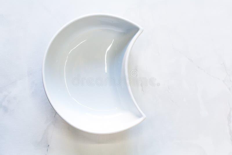 Ciotola bianca sotto forma di una mezzaluna Spazio per il logo immagine stock libera da diritti
