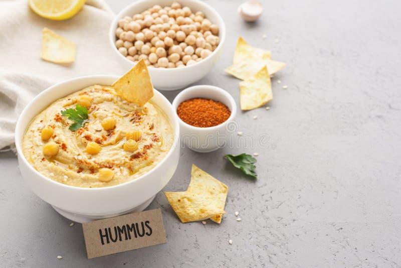 Ciotola casalinga di hummus con le patatine fritte, i ceci, il prezzemolo e la paprica fotografia stock