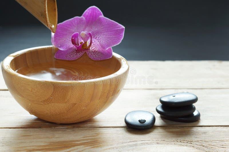 Ciotola, che versa l'acqua trasparente dal bambù, dai fiori dell'orchidea e dalle pietre per un massaggio caldo su una tavola di  immagini stock