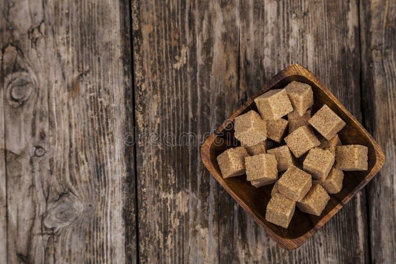 Ciotola con i cubi dello zucchero di canna fotografie stock
