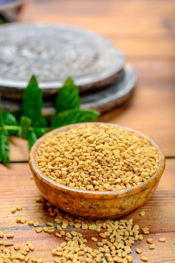 Ciotola con i semi di fieno greco vicino su, usato per la cottura e il traditi fotografia stock libera da diritti