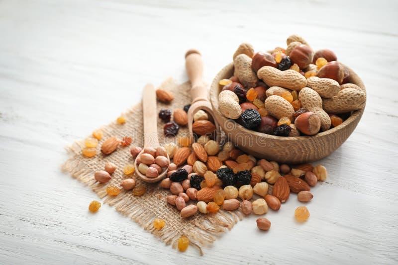 Ciotola con i vari dadi saporiti e frutti secchi sulla tavola di legno immagini stock libere da diritti
