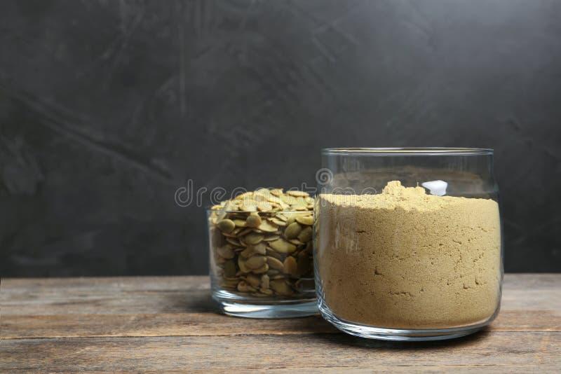 Ciotola con la farina ed i semi della zucca sulla tavola di legno immagine stock libera da diritti