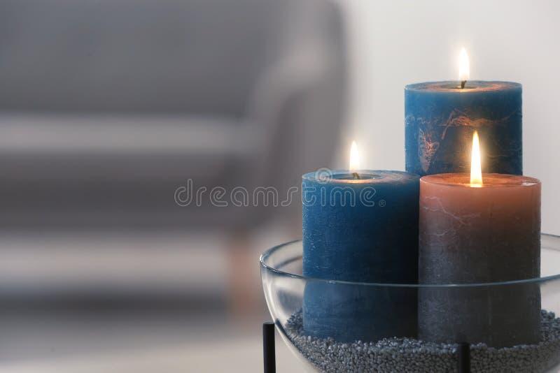Ciotola con le candele brucianti su fondo vago immagini stock libere da diritti