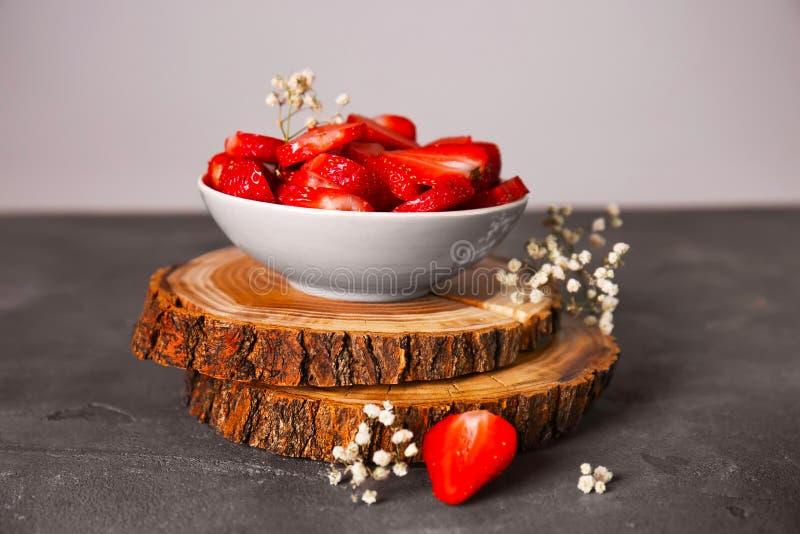 Ciotola con le fragole rosse mature sulla tavola contro fondo leggero fotografia stock