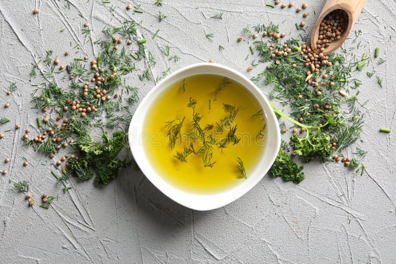 Ciotola con olio d'oliva e le erbe su fondo grigio, vista superiore immagini stock