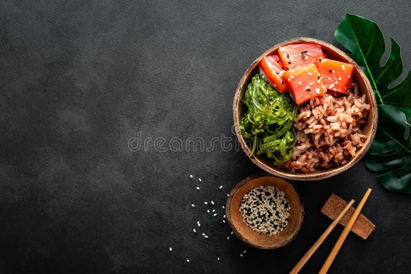 Ciotola del colpo con il pesce, l'insalata di chuka ed il riso di color salmone crudi in ciotole della noce di cocco su fondo ner fotografia stock libera da diritti