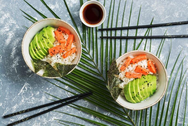 Ciotola del colpo con riso e le verdure di color salmone su fondo grigio con le foglie di palma Insalata hawaiana tradizionale de immagini stock