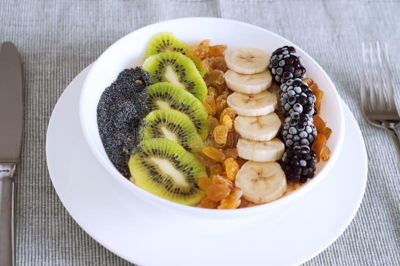 Ciotola del frullato della farina d'avena dell'uva passa della mora della banana del kiwi fotografia stock