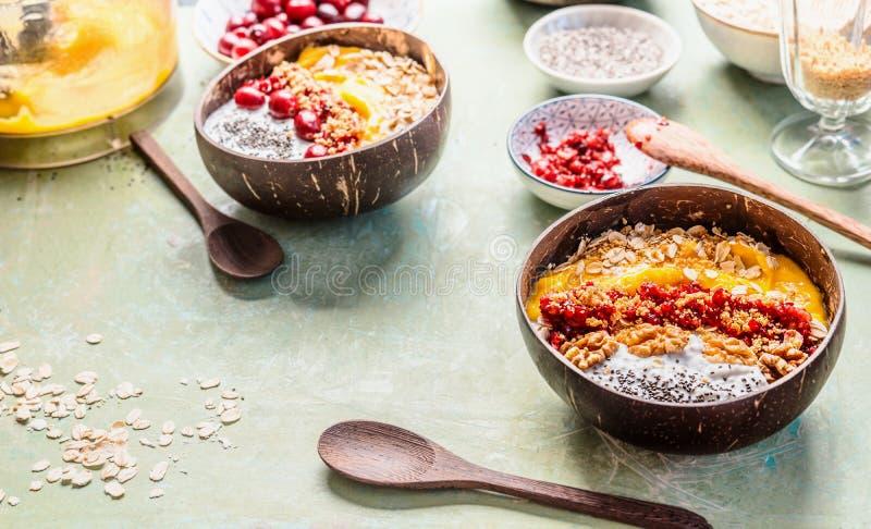 Ciotola del frullato della prima colazione nelle coperture della noce di cocco, completate con i fiocchi di avena e bacche e dadi fotografia stock