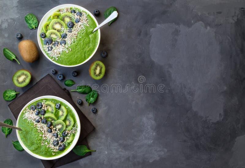 Ciotola del frullato di verde della prima colazione con il kiwi, i mirtilli ed i semi di girasole fotografie stock libere da diritti