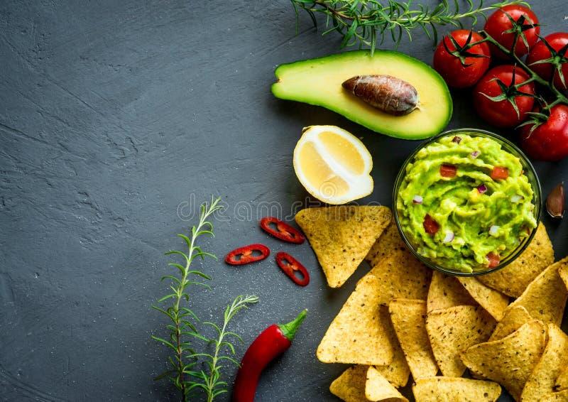 Ciotola del guacamole con gli ingredienti ed i chip di tortiglia su una tavola di pietra Immagine di vista superiore Copyspace pe immagini stock