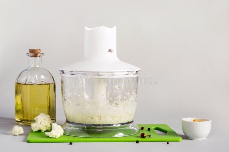 Ciotola del miscelatore con il riso e le spezie appeni preparato del cavolfiore fotografia stock