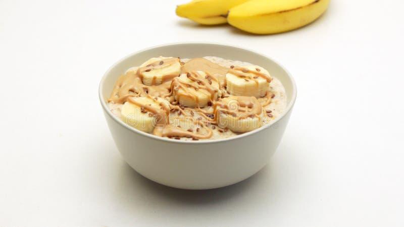Ciotola del porridge della farina d'avena con il burro di dado e della banana immagine stock libera da diritti
