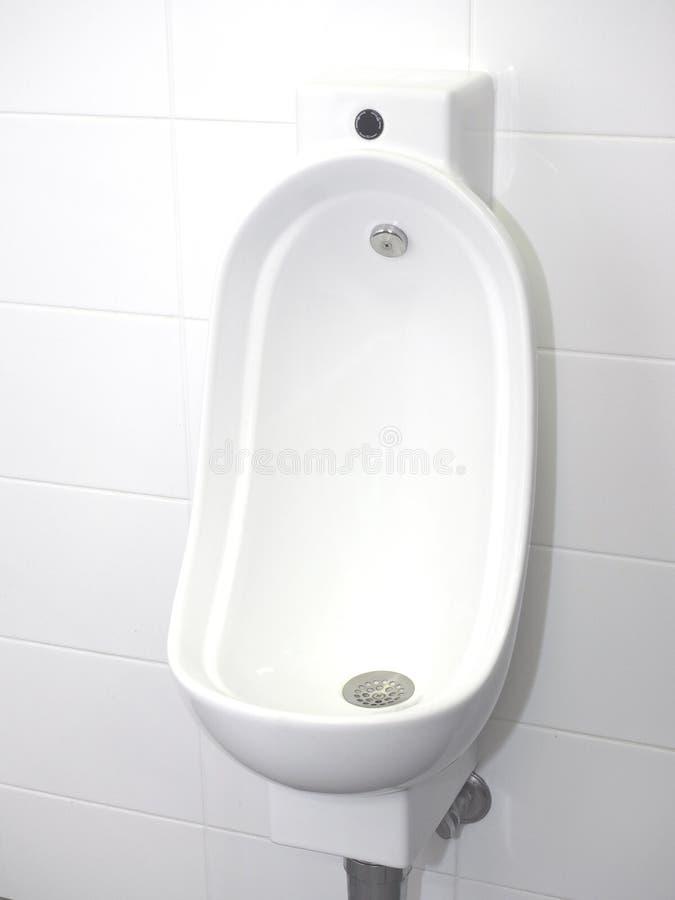 Ciotola dell'orinale con vampata mani libere automatica in un lavabo incontaminato fotografia stock