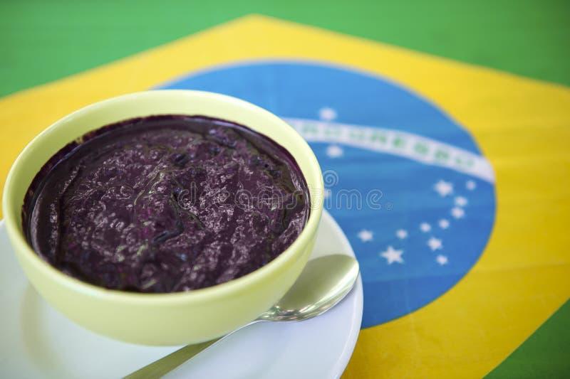 Ciotola di Acai Açaí Jussara sulla bandiera brasiliana immagini stock libere da diritti