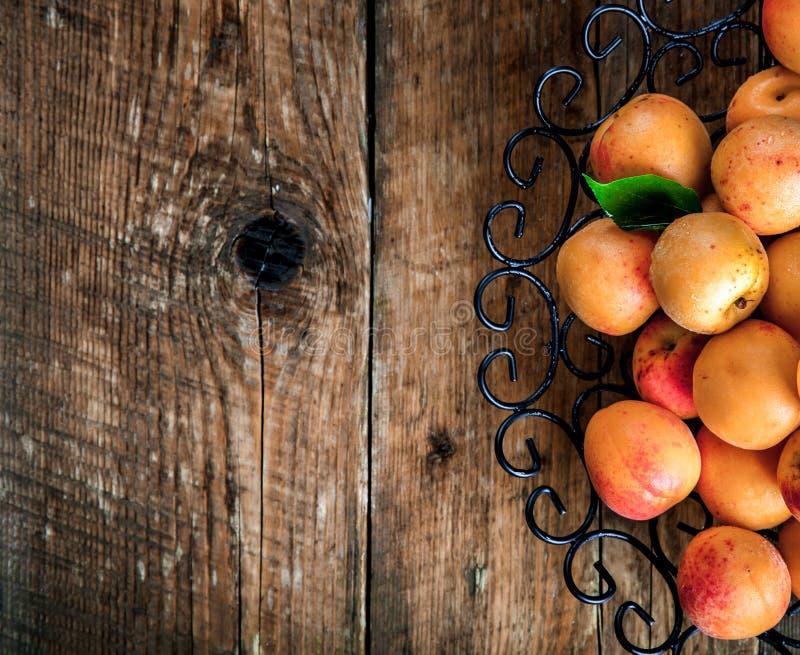 Ciotola di albicocche raccolte Albicocche fresche su fondo di legno immagine stock