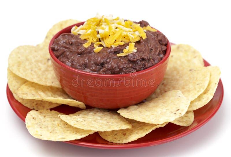 Ciotola di Bean Dip nero con i chip su un fondo bianco fotografia stock libera da diritti