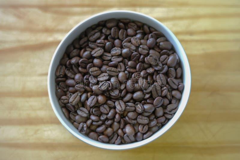 Ciotola di chicchi di caffè sulla tavola di legno fotografia stock