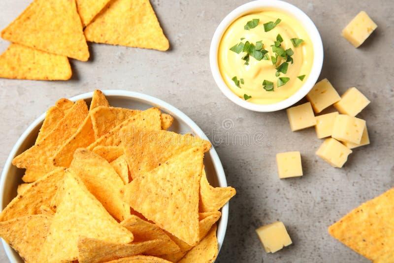 Ciotola di chip messicani deliziosi dei nacho e salsa di formaggio sulla tavola grigia fotografia stock libera da diritti