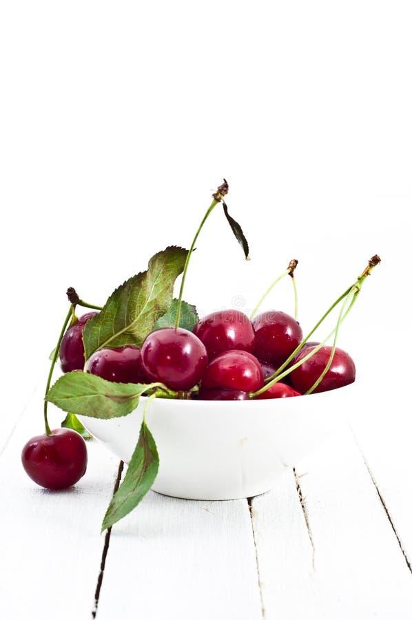 Ciotola di ciliege rosse fresche in piatto bianco fotografie stock libere da diritti
