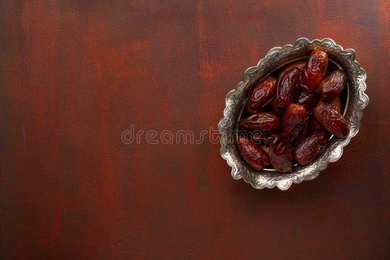 Ciotola di date su una tavola di legno marrone-rosso dipinta Vista superiore immagine stock
