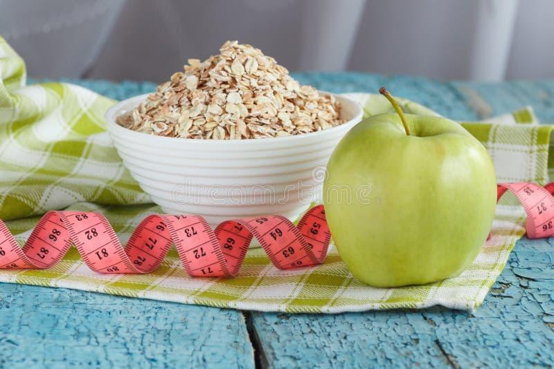 Ciotola di farina d'avena, di mela verde e di misurazione del nastro immagini stock