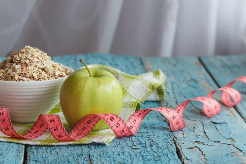 Ciotola di farina d'avena, di mela verde e di misurazione del nastro fotografia stock libera da diritti