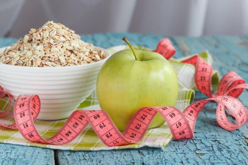 Ciotola di farina d'avena, di mela verde e di misurazione del nastro fotografia stock