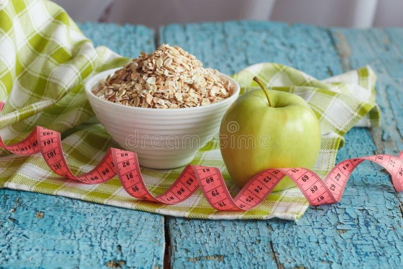 Ciotola di farina d'avena, di mela verde e di misurazione del nastro fotografie stock libere da diritti