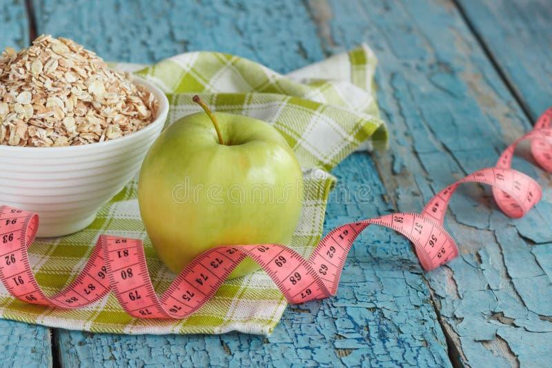 Ciotola di farina d'avena, di mela verde e di misurazione del nastro fotografie stock