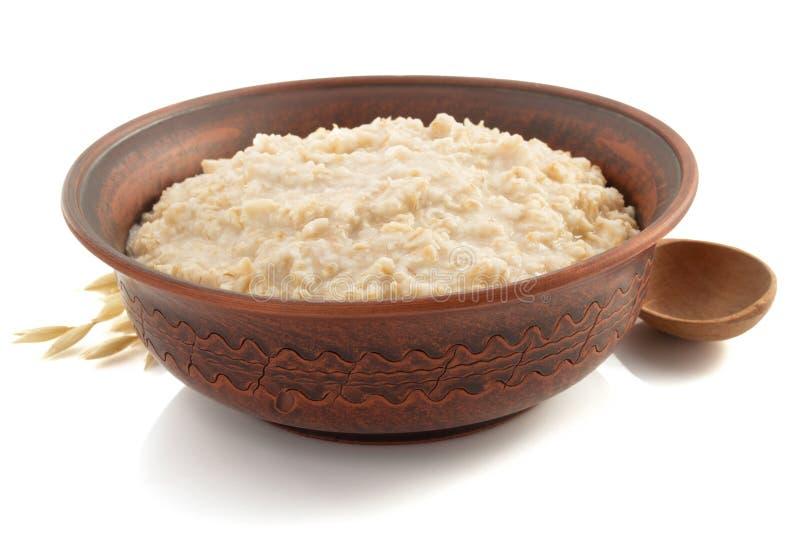 Ciotola di farina d'avena su bianco immagine stock