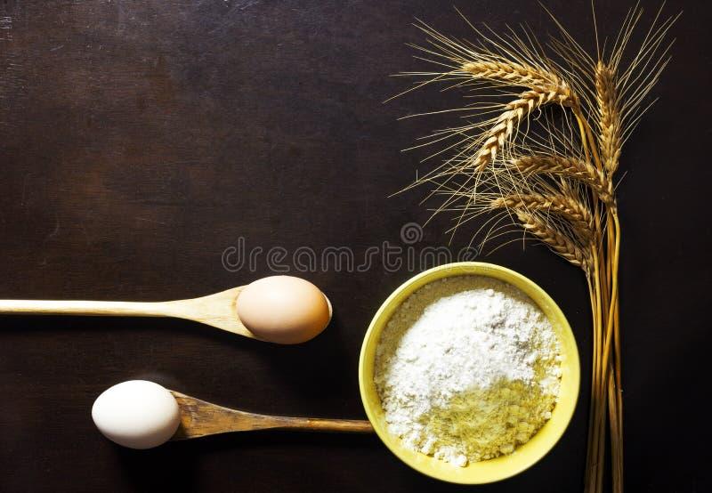 Ciotola di farina di frumento con le orecchie e le uova del grano su backgroun di legno fotografia stock libera da diritti