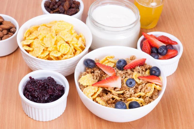 Ciotola di fiocchi di granturco con i cereali da prima colazione freschi e del bacca fotografia stock