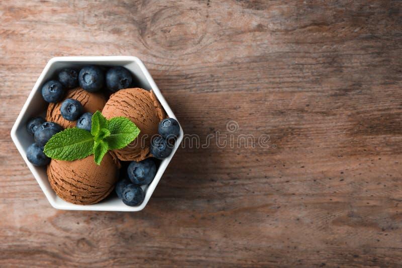 Ciotola di gelato e di mirtilli del cioccolato sulla tavola di legno, vista superiore immagini stock libere da diritti