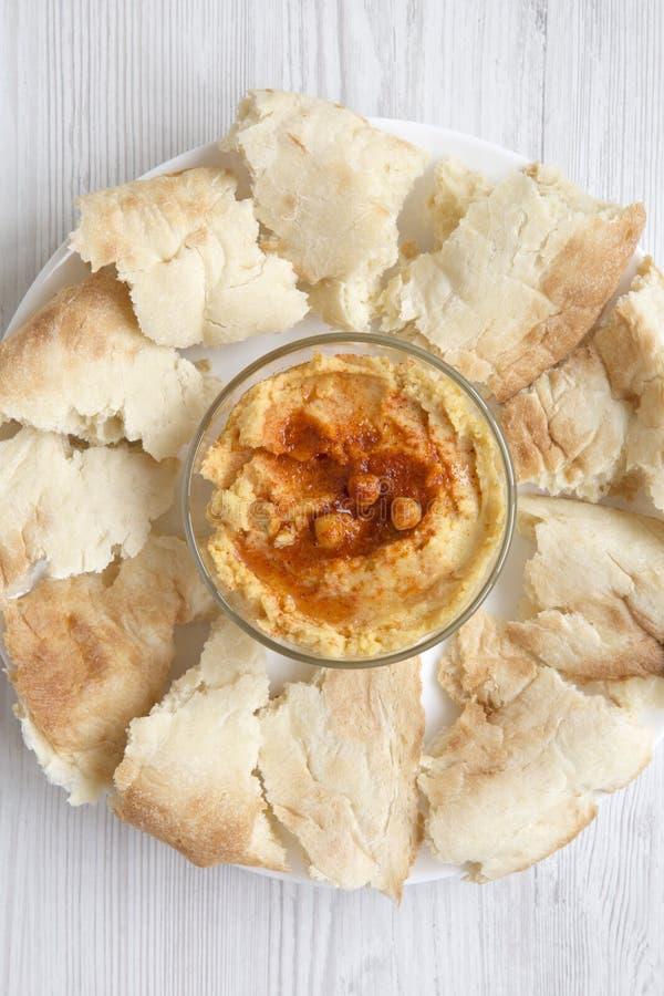 Ciotola di hummus con i ceci, la paprica, l'olio d'oliva ed il pane della pita sul piatto bianco sopra fondo di legno bianco, vis fotografia stock libera da diritti