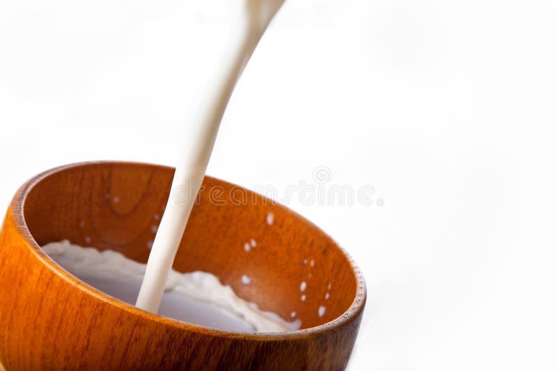 Ciotola con il versamento del latte fotografia stock