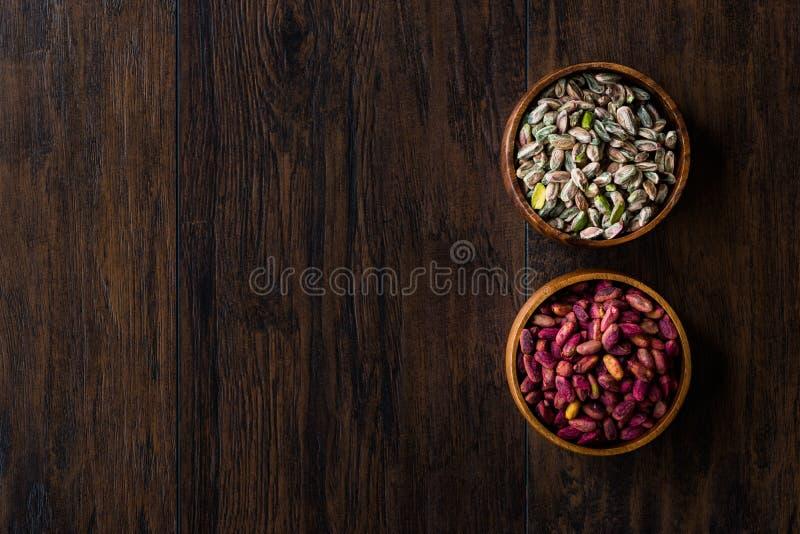 Ciotola di legno cruda ed arrostita di pistacchi sbucciati senza Shell/senza Shell fotografie stock