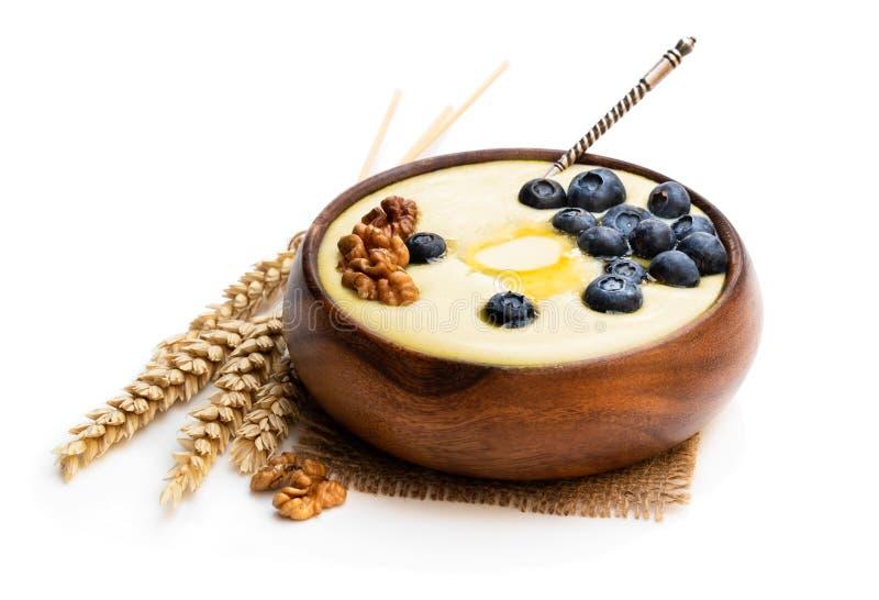 Ciotola di legno di porridge del semolino con il mirtillo e la noce isolati su bianco immagini stock libere da diritti
