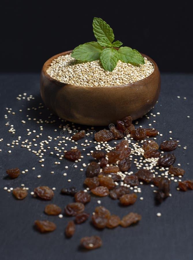 Ciotola di legno riempita di quinoa sull'immagine di sfondo nera immagini stock libere da diritti