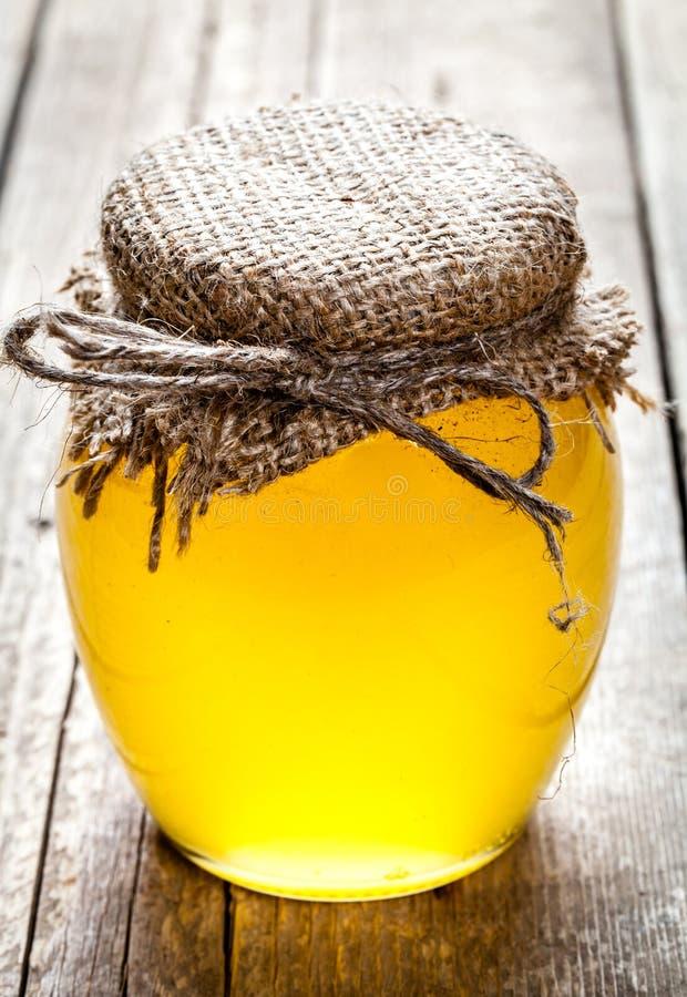 Ciotola di miele sulla tavola di legno Simbolo di medicina vivente e naturale sana Aromatico e saporito immagine stock