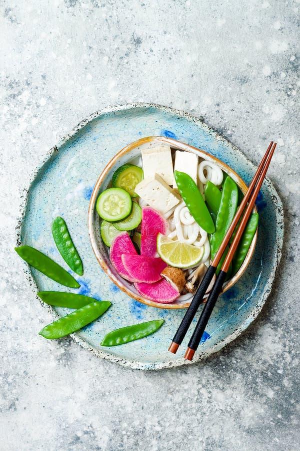 Ciotola di minestra asiatica delle tagliatelle del udon del vegano con lo zenzero ed i funghi brodo, tofu, piselli improvvisi, zu immagine stock libera da diritti